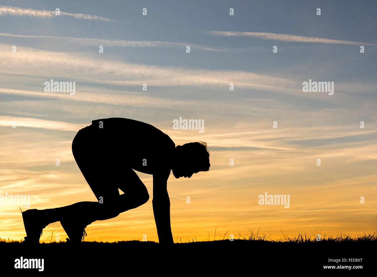 Silhouette, cielo notturno, uomo accovacciato prima di sprint, atletica leggera Immagini Stock