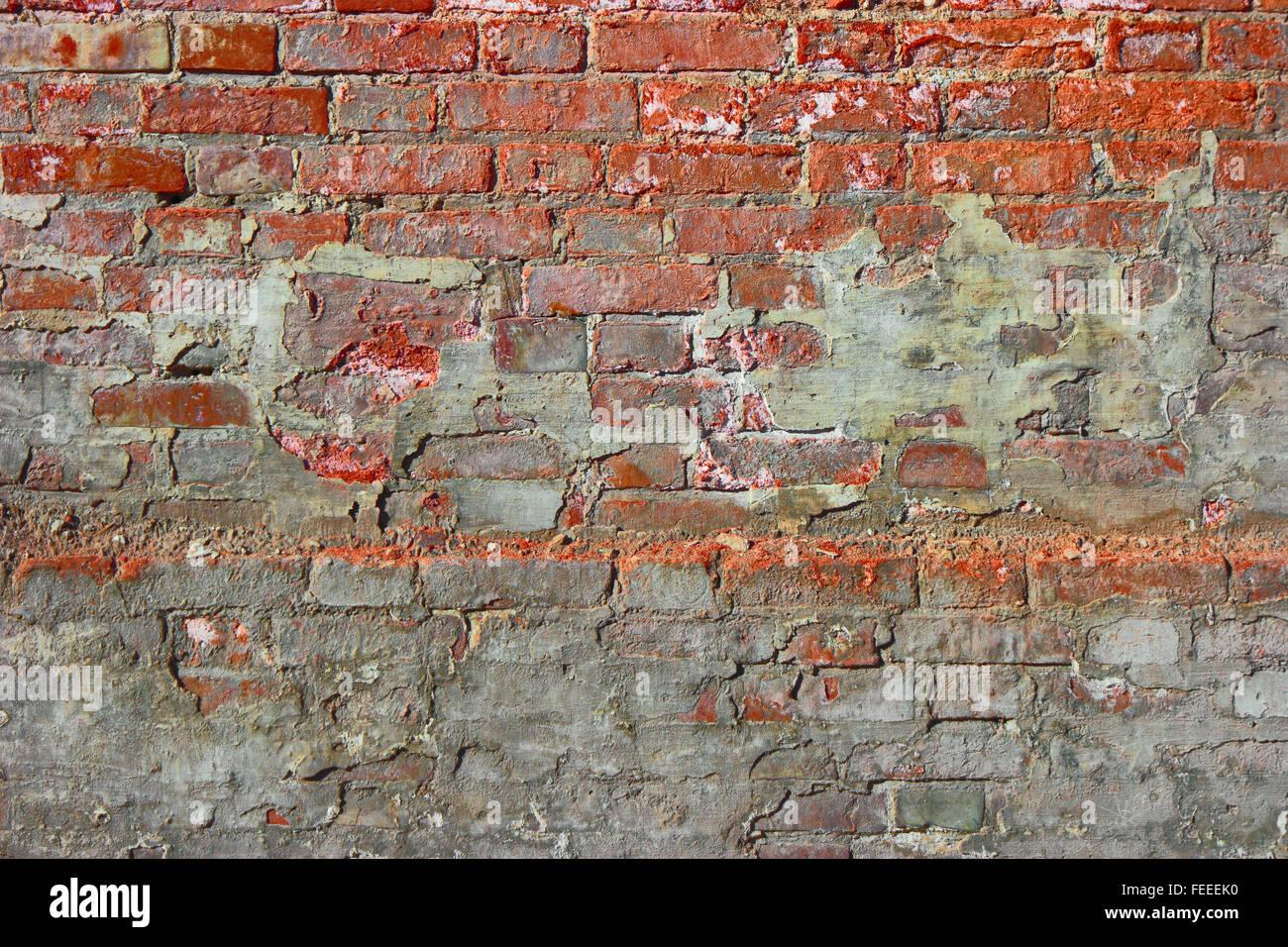 Vecchio danneggiato un muro di mattoni con intonaco. Rosso sporco vecchio muro di mattoni in ...