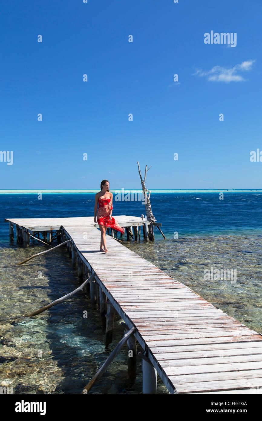 Donna che cammina sul molo, Tetamanu, Fakarava, isole Tuamotu, Polinesia Francese Immagini Stock