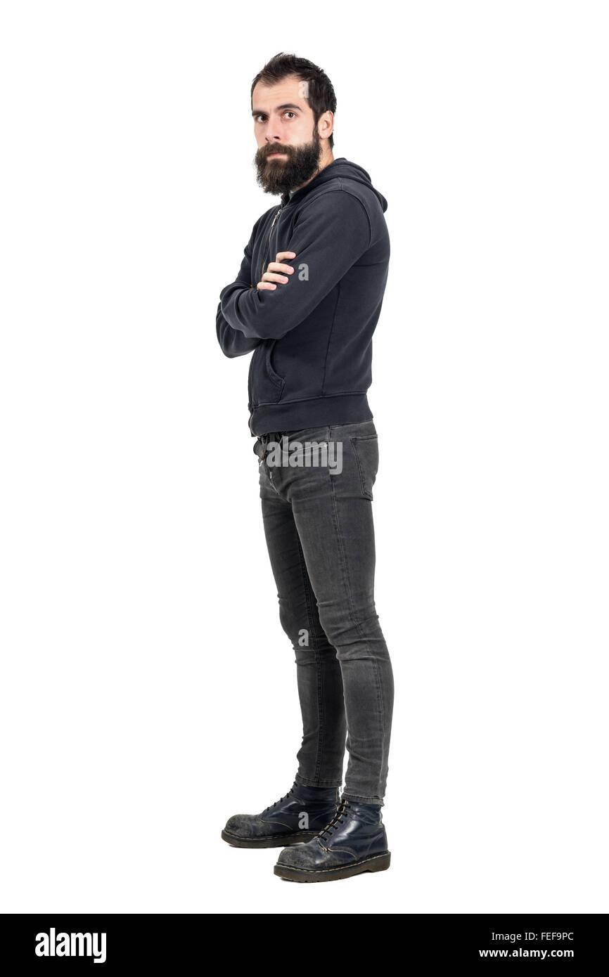 Fiducioso grave punker indossare stivali vecchi e nero felpa con cappuccio guardando la fotocamera. Corpo pieno Immagini Stock