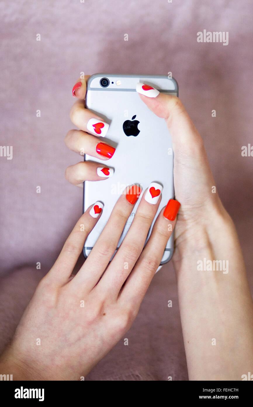 Mani di Apple i Phone 6 con le unghie dipinte di cuori Immagini Stock