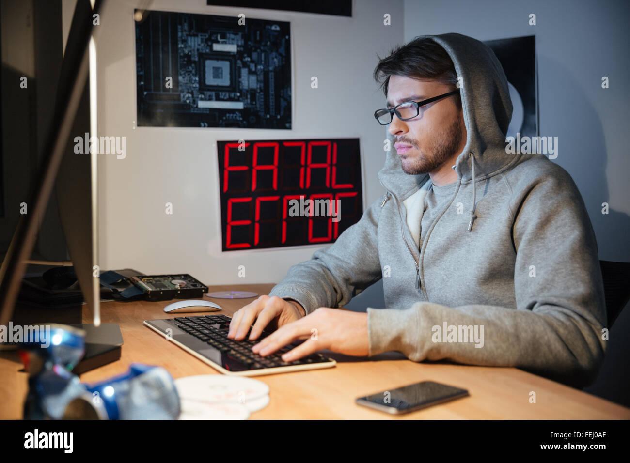 Bel giovane uomo in felpa con cappuccio di seduta e digitando sulla tastiera del computer a casa Immagini Stock