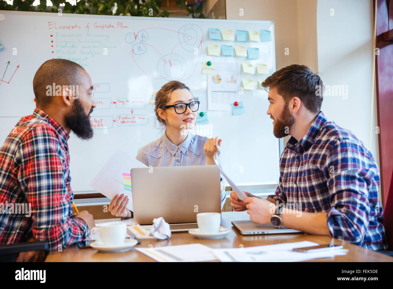 Gruppo serio di giovani che lavorano sulla riunione di affari insieme Immagini Stock