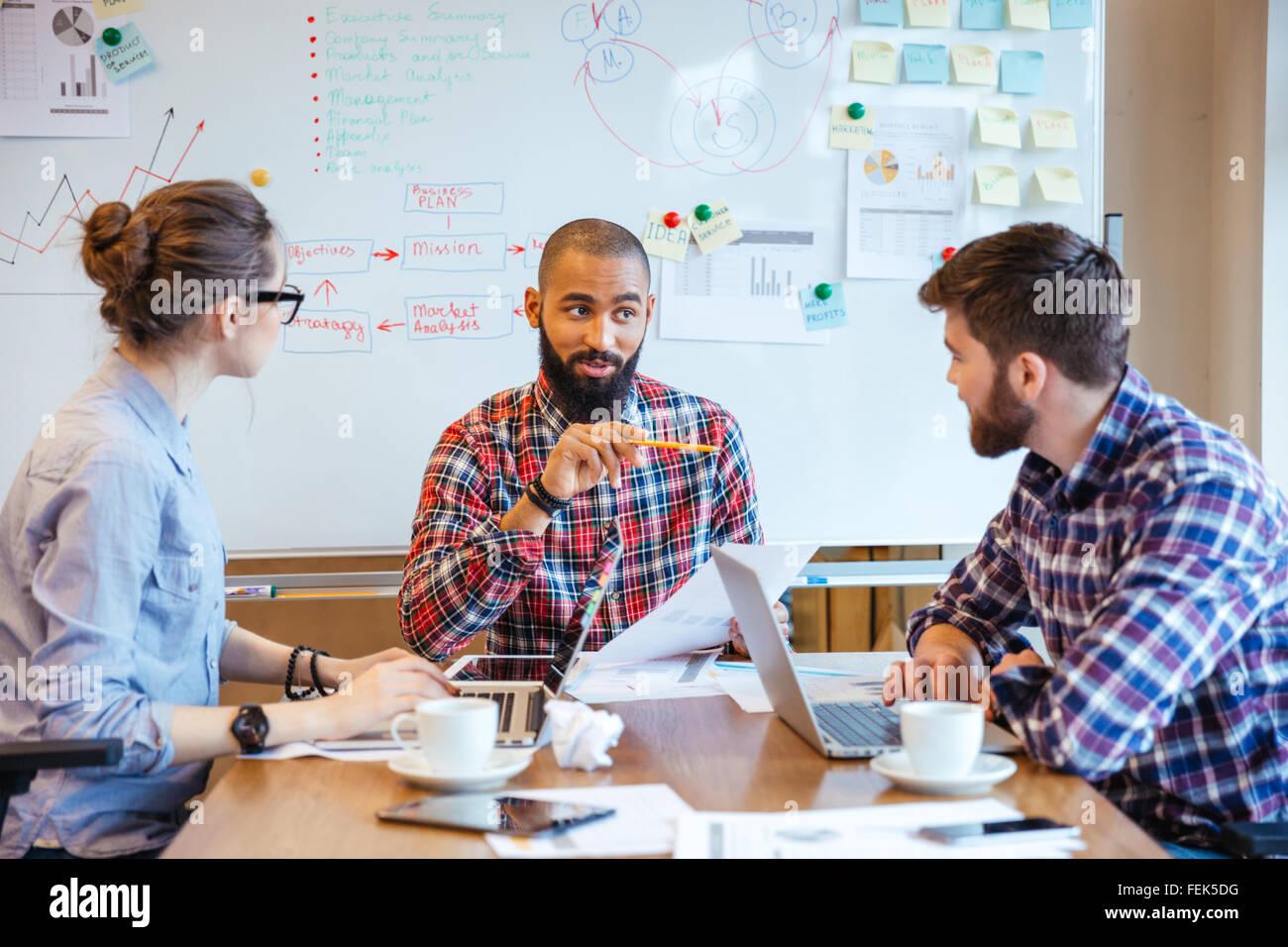 Un gruppo di giovani creativi la creazione di un nuovo progetto insieme nella sala conferenze Immagini Stock