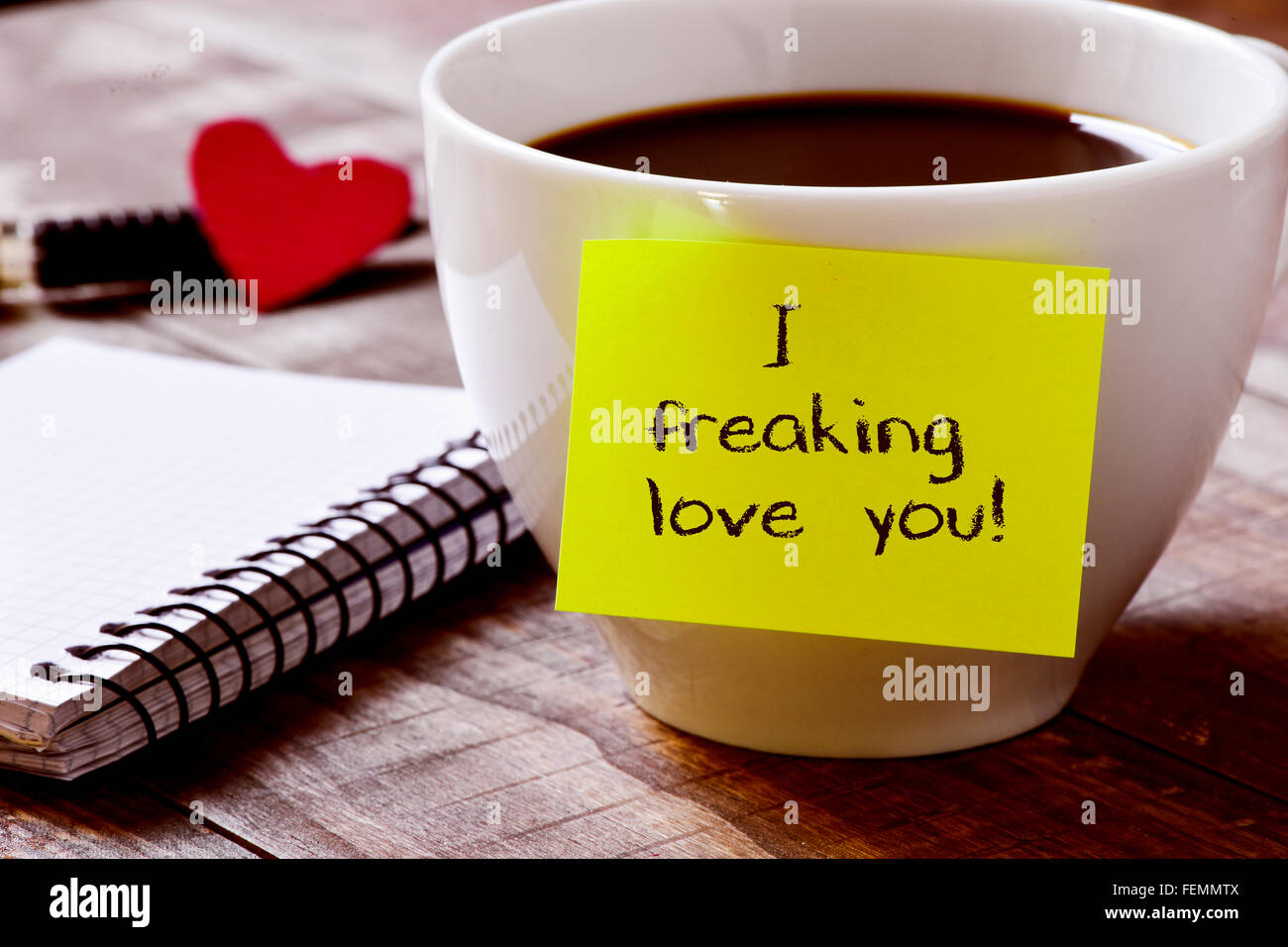 Primo piano di un bigliettino giallo con il testo che ho freaking amore è attaccato ad una tazza di caffè, Immagini Stock