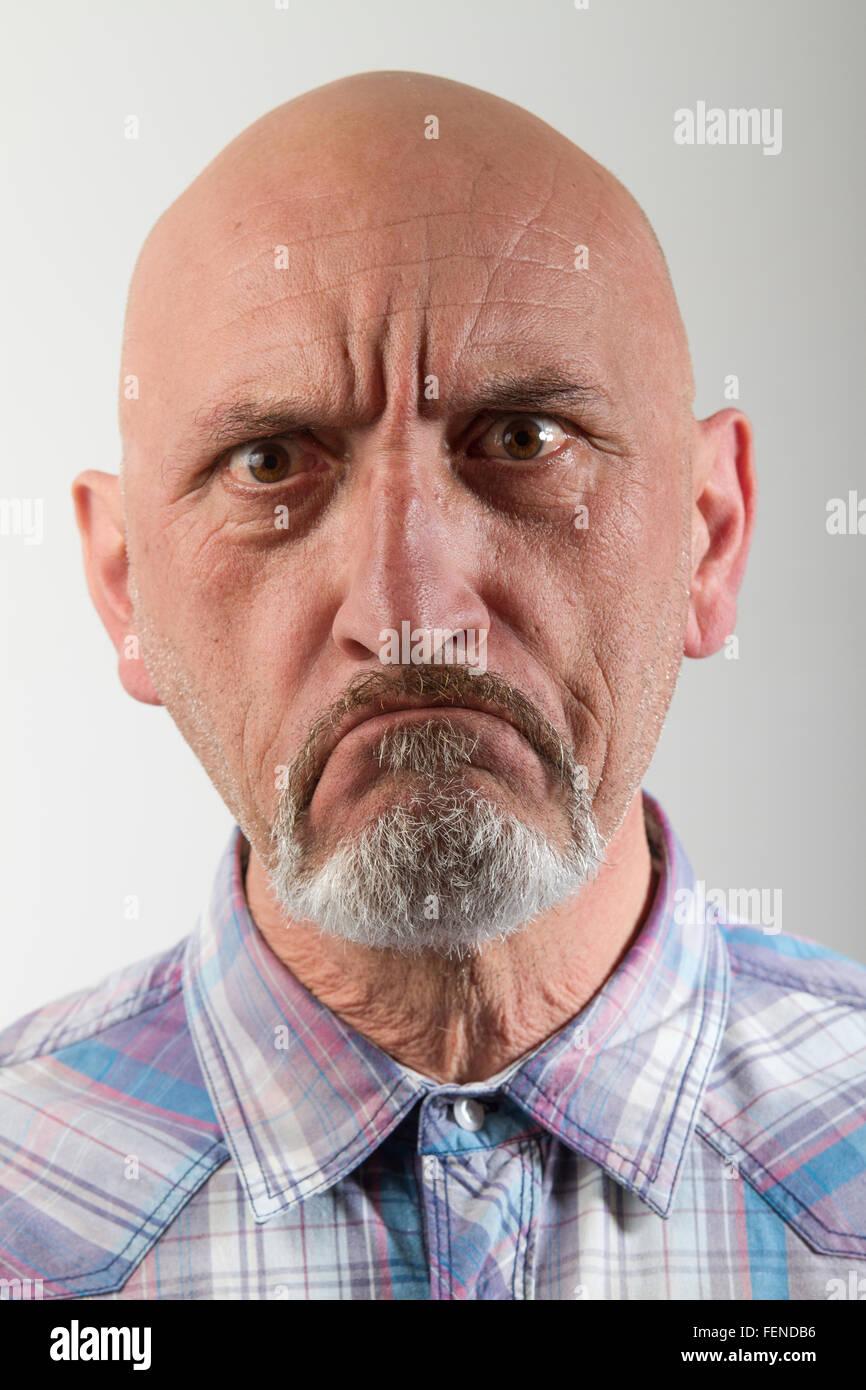 In primo piano il ritratto di uomo arrabbiato contro uno sfondo grigio Immagini Stock