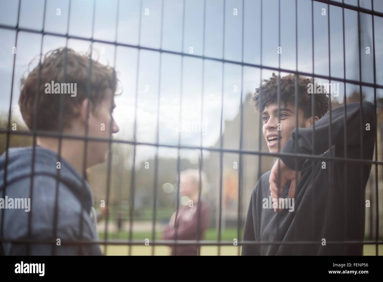 Due giovani uomini appoggiata contro la recinzione, parlando Immagini Stock