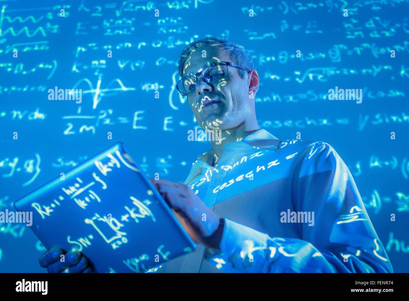 Scienziato con tavoletta digitale e proiettata dati matematici Immagini Stock