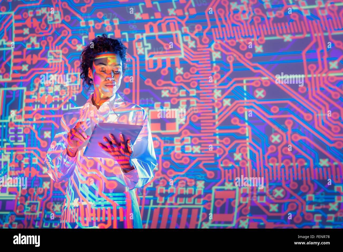 Donna scienziato utilizzando tavoletta digitale con grafica del circuito elettronico di proiezione Immagini Stock