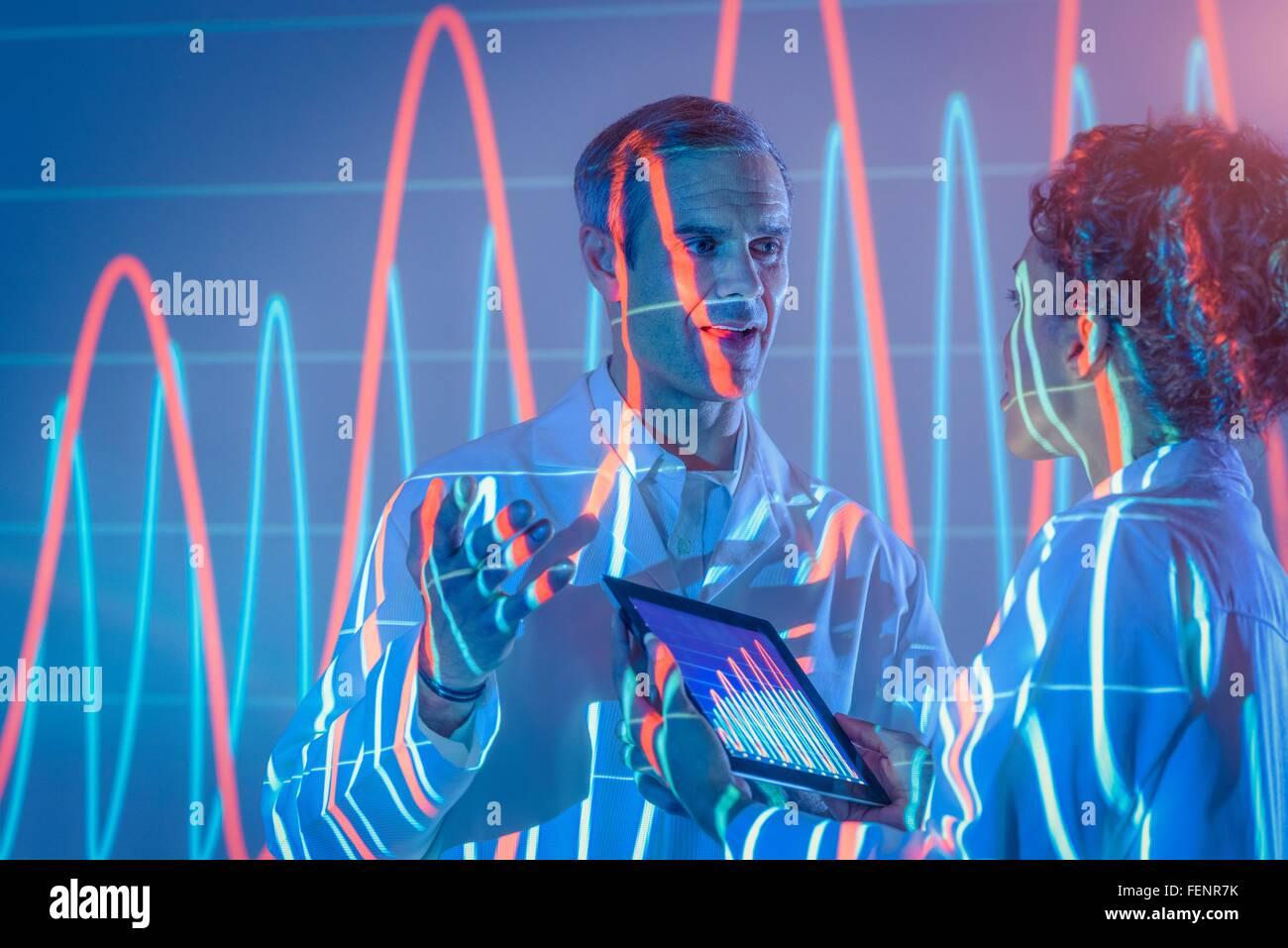 Gli scienziati in discussione con grafica di proiezione dei dati Immagini Stock