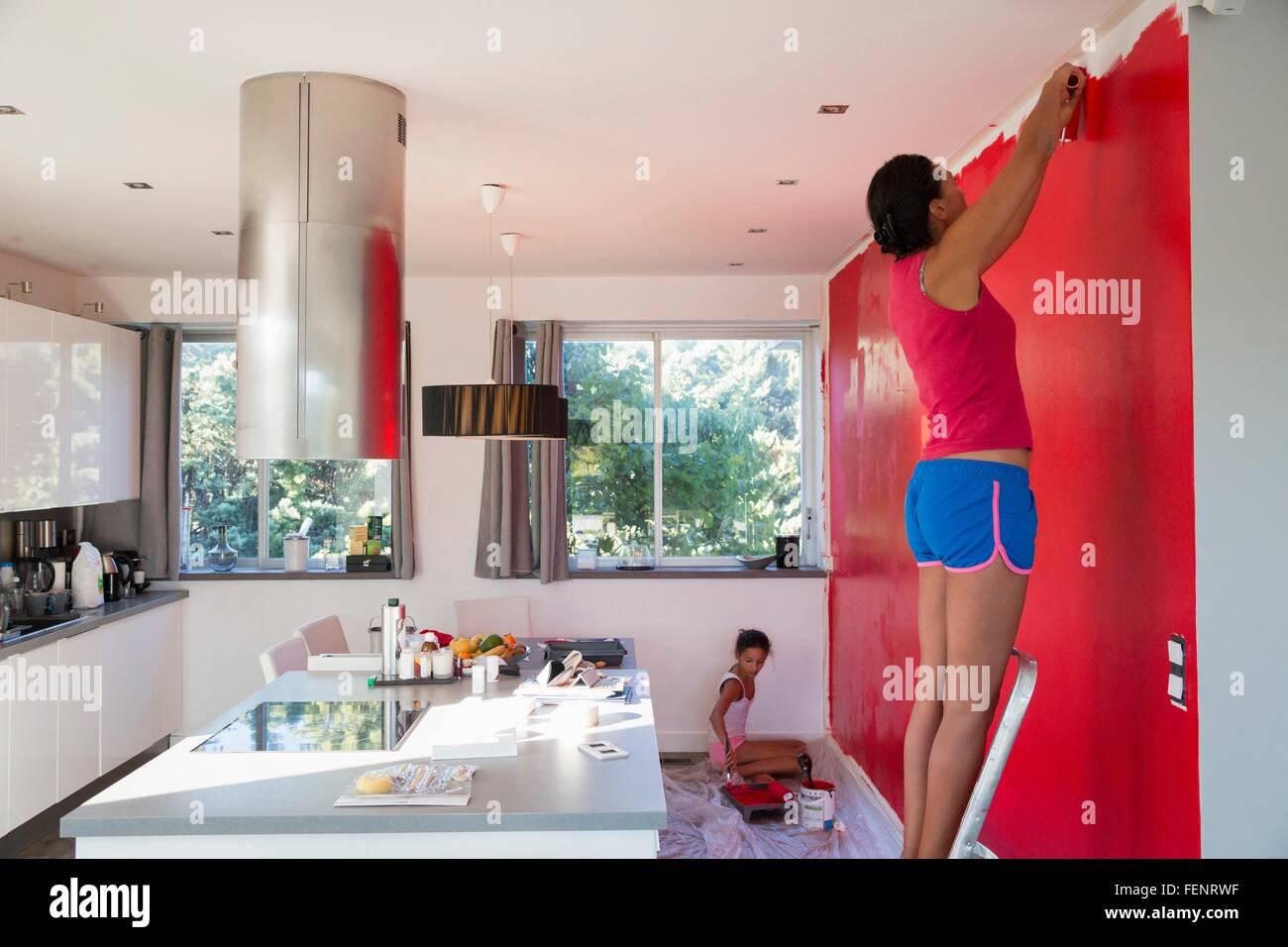 Ragazza madre e pittura parete cucina rosso con rulli di vernice ...
