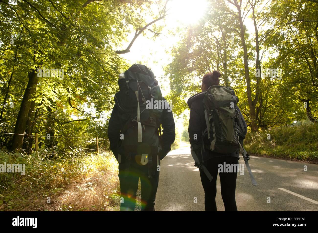 Vista posteriore del giovane escursionismo giovane sulla strada rurale Immagini Stock