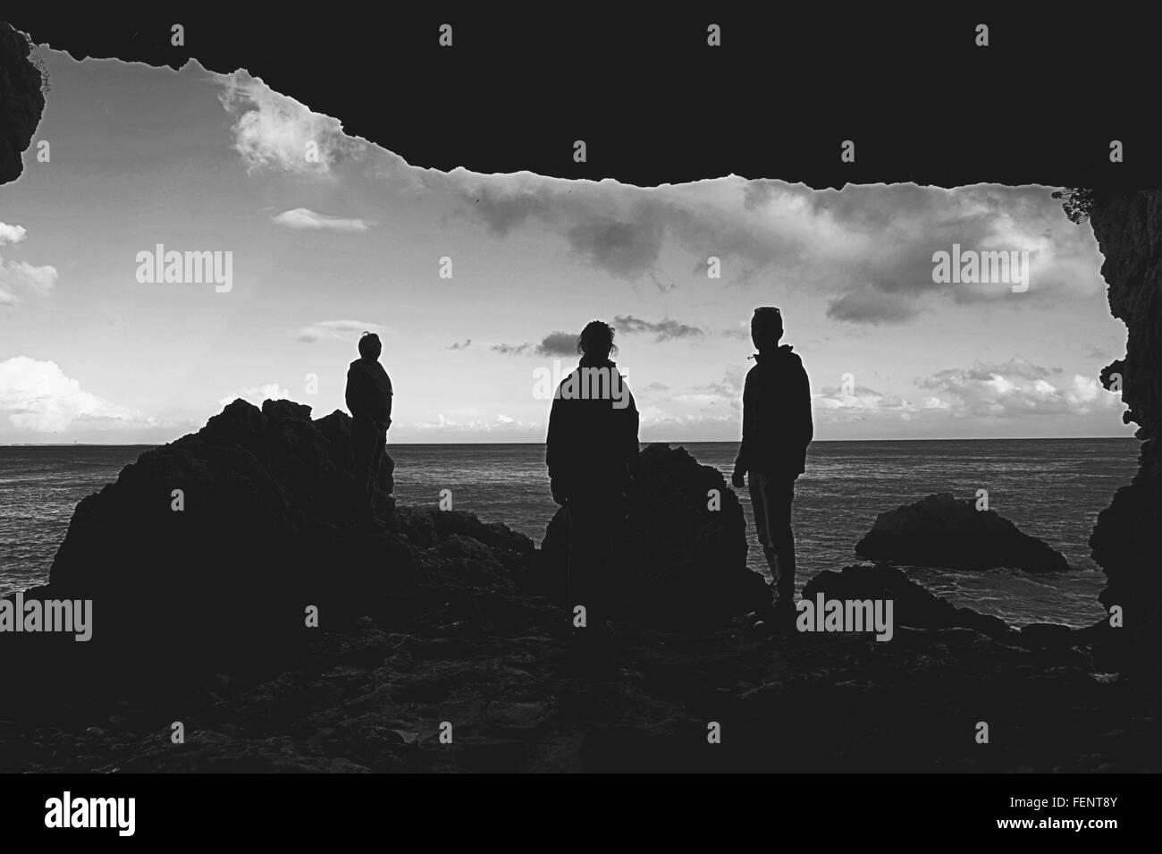 Silhouette persone in piedi presso la spiaggia da rocce Immagini Stock