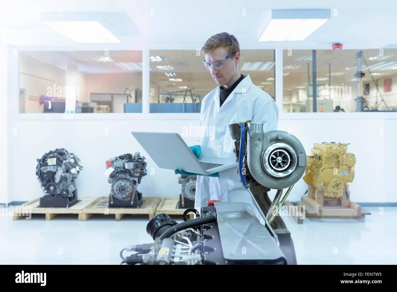 Scienziato utilizzando laptop nel caricabatterie turbo automotive laboratorio di ricerca Immagini Stock