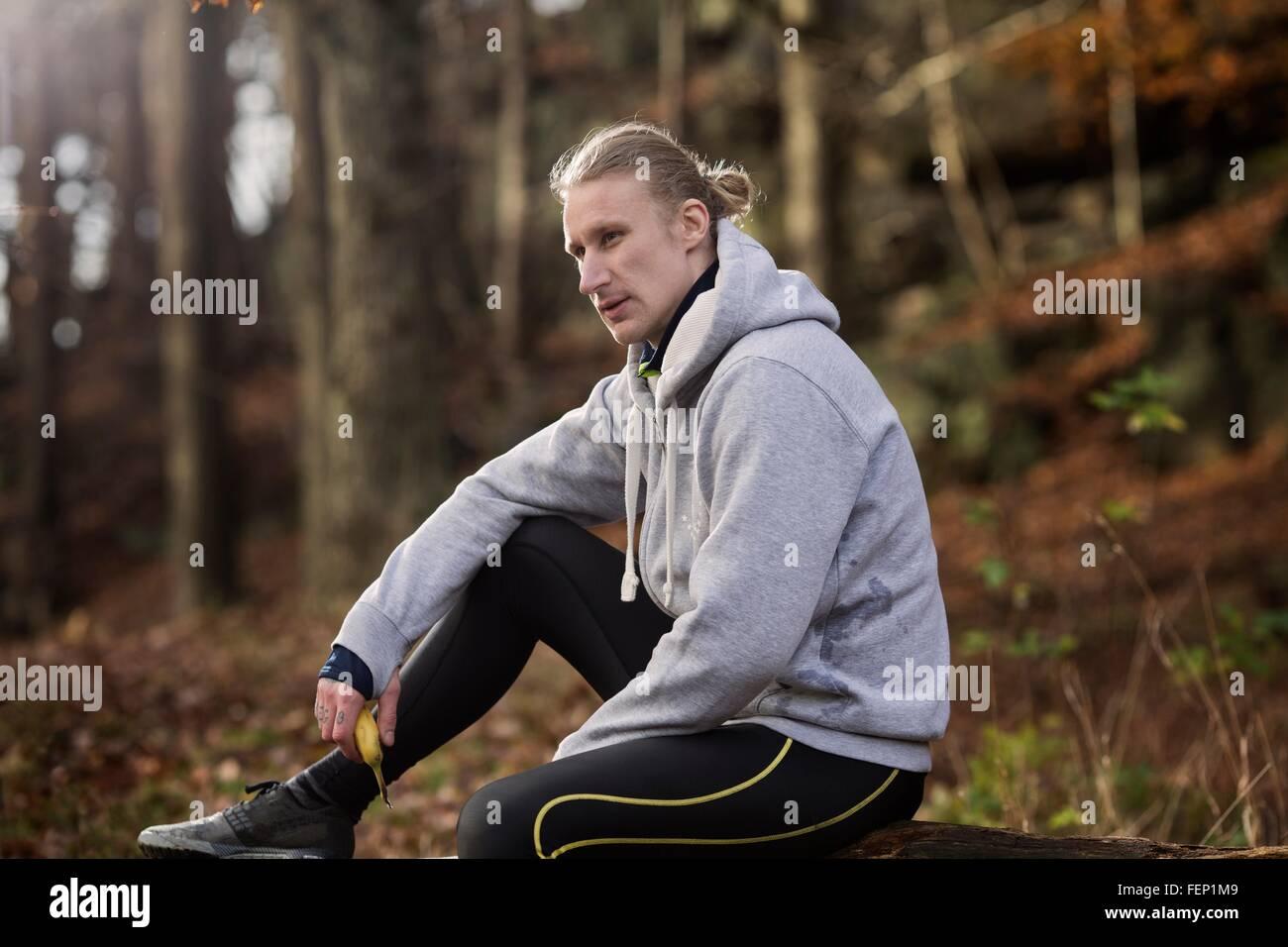 Metà uomo adulto di indossare abbigliamento sportivo azienda banana guardando lontano Immagini Stock
