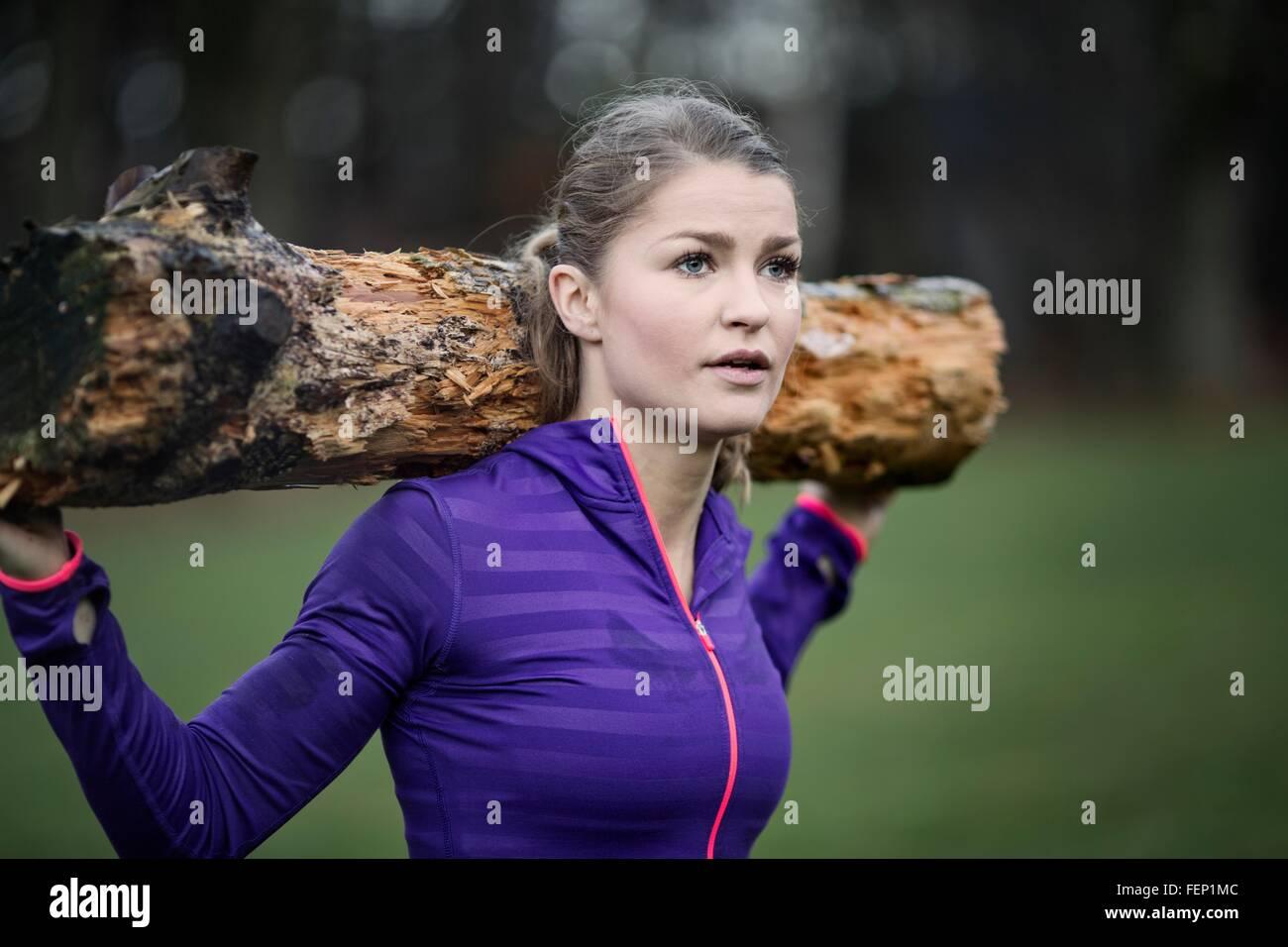 Giovane donna che trasportano ramo di albero sullo spallamento guardando lontano Immagini Stock
