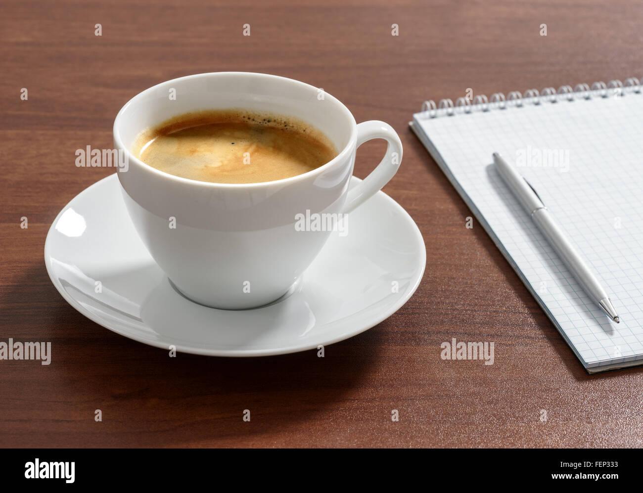 Tazza di caffè aromatico americano con il blocco note e penna. Immagini Stock