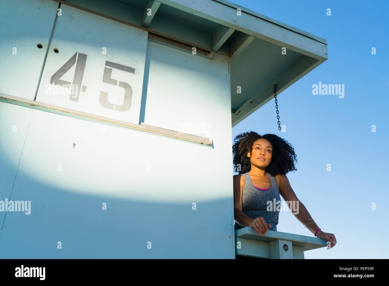 Metà donna adulta in piedi sul look out torre in spiaggia, guardando a vista Immagini Stock