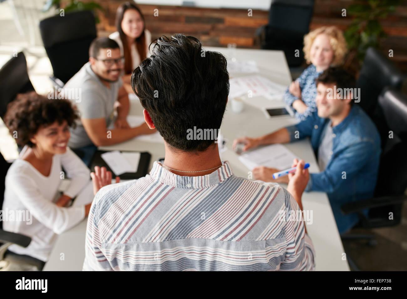 Vista posteriore del ritratto di uomo che spiega le idee di business per i colleghi durante una riunione nella sala Immagini Stock