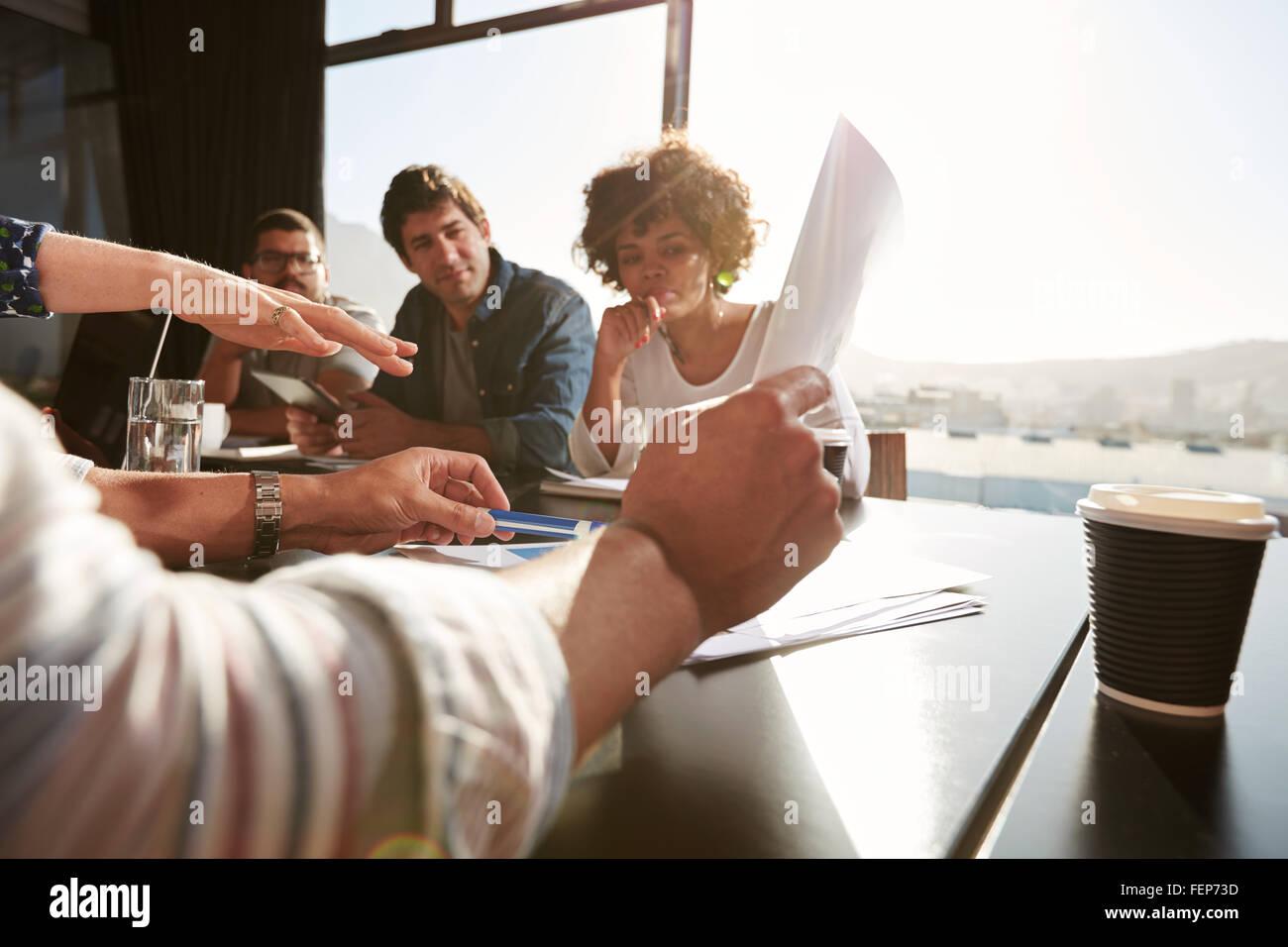 Le mani del giovane uomo e donna spiegando business plan ai colleghi, team creativo avente una riunione in ufficio. Immagini Stock