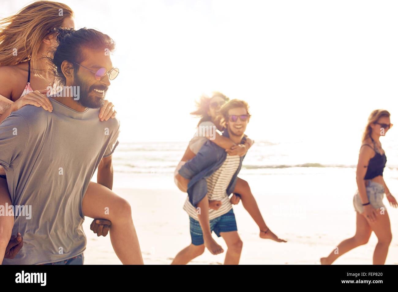 Gruppo di amici divertendosi sulla spiaggia, giovani uomini piggybacking donne sulla riva del mare. Razza mista Immagini Stock