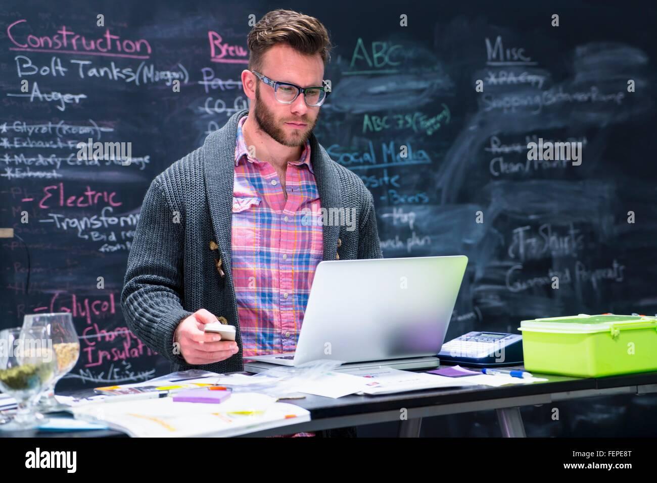 Giovane Uomo nel posto di lavoro utilizzando laptop smartphone di contenimento Immagini Stock