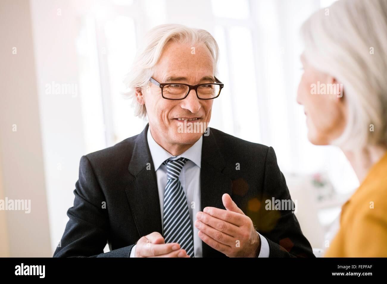 Senior uomo che indossa la maglietta, cravatta e giacca tuta parlando di donna senior Immagini Stock
