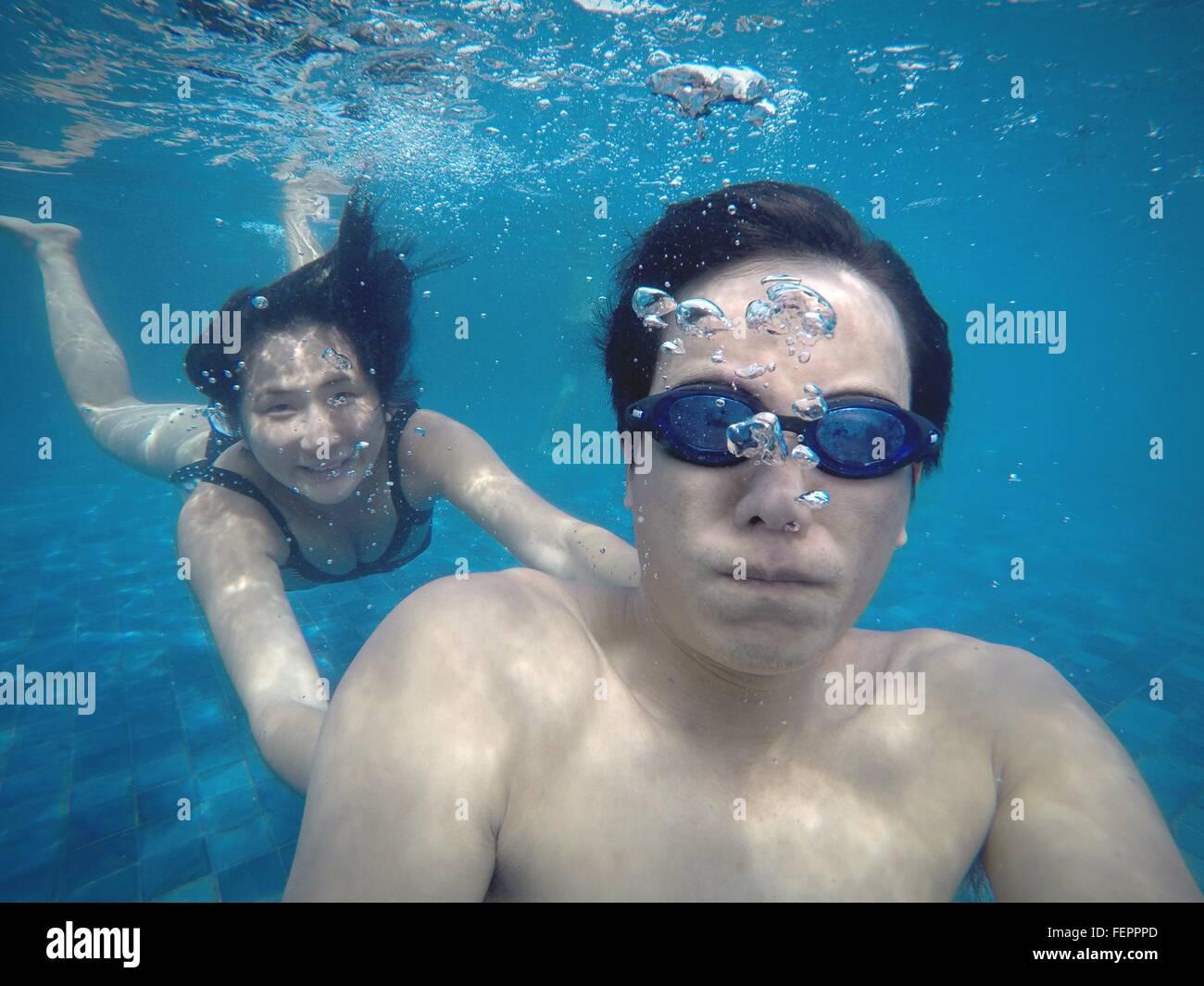 L'uomo con la donna sorridente di nuoto in piscina Foto Stock