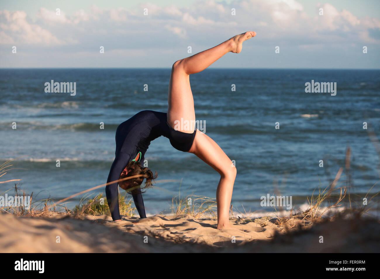 Un ginnasta sta facendo la sua routine sulla spiaggia in Sud Africa. Immagini Stock
