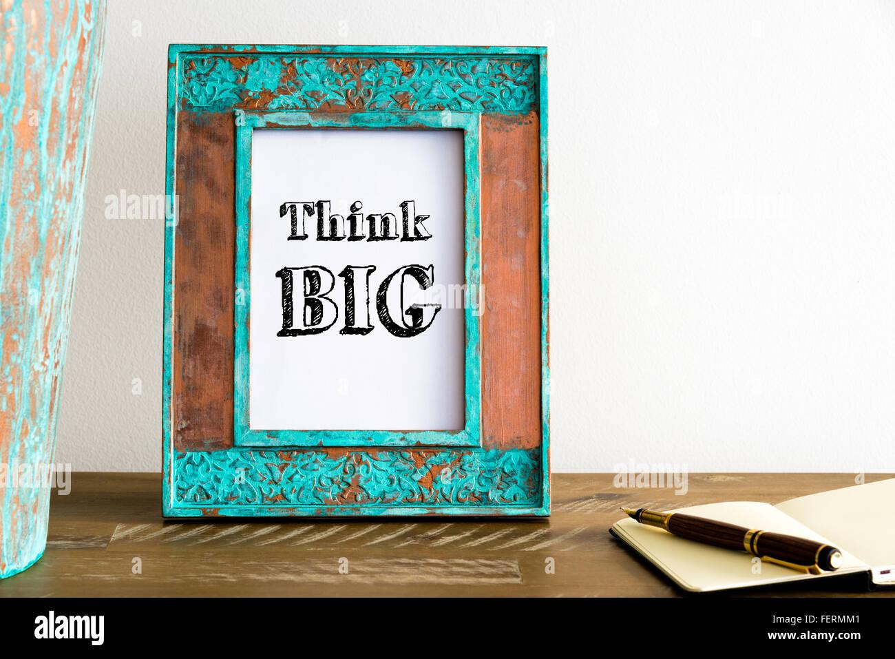 Vintage photo frame su un tavolo di legno oltre il muro bianco lo sfondo con il messaggio motivazionale PENSARE Immagini Stock