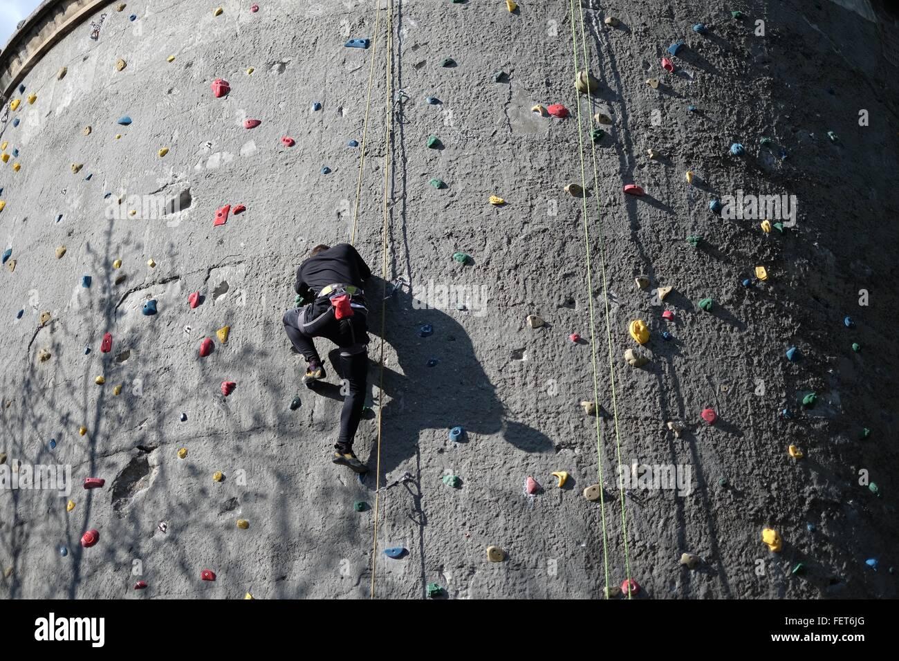 Basso Angolo di visione dell uomo sulla parete di arrampicata Immagini Stock