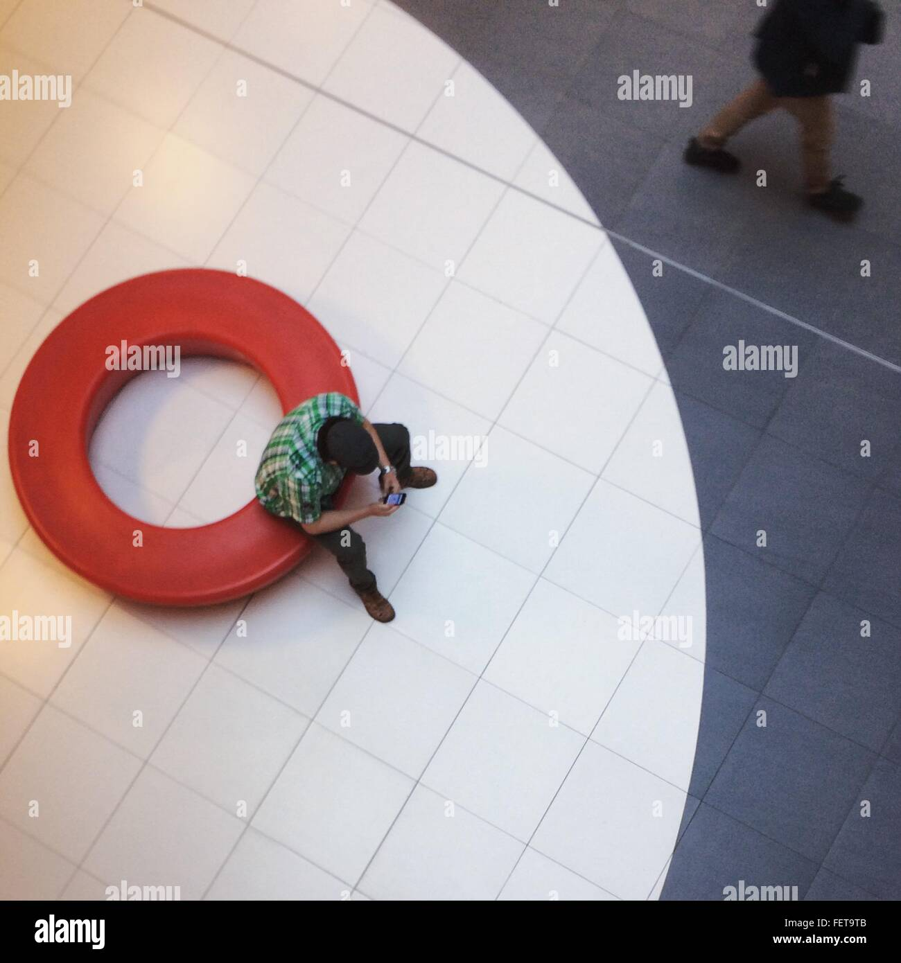 Elevato angolo di visione dell'uomo utilizzando il telefono cellulare nella Lobby Immagini Stock