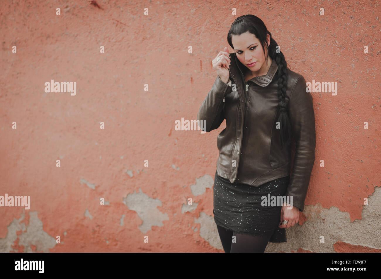 Donna appoggiata sulla parete Immagini Stock