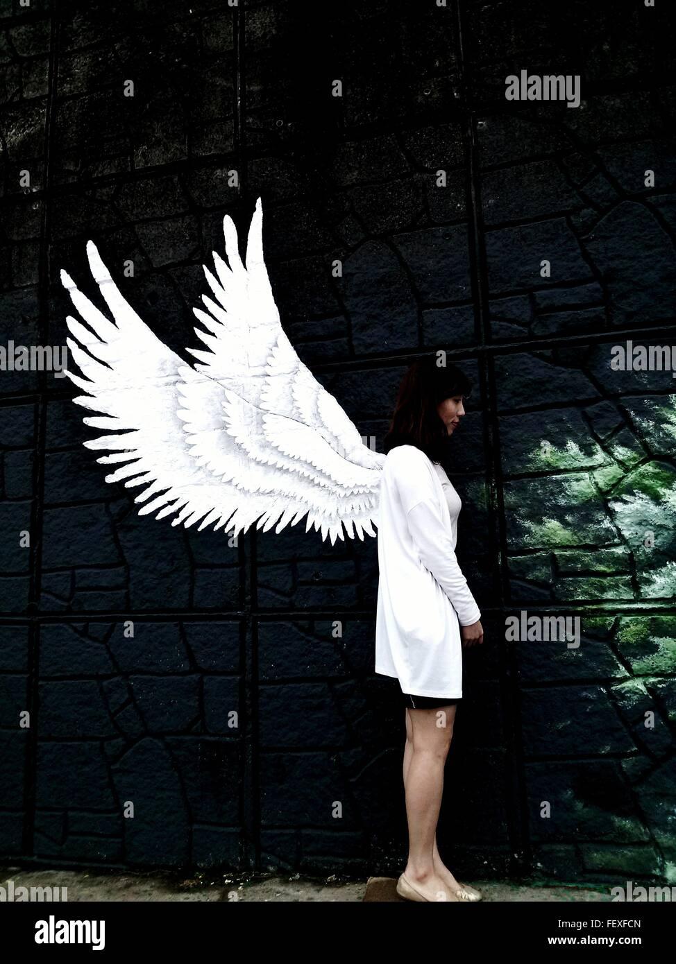 Donna in piedi contro il dipinto sul muro Immagini Stock