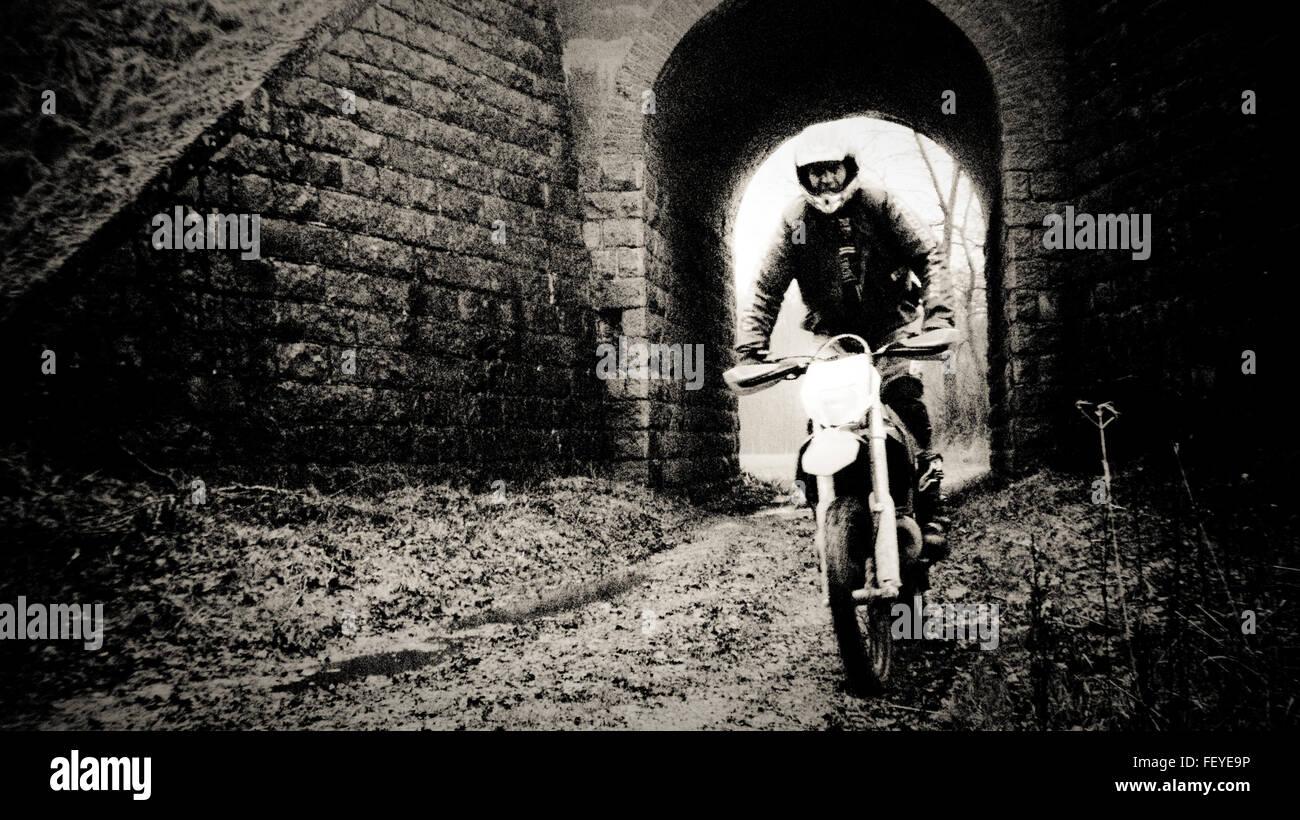 Uomo in sella motocicletta su strada sterrata contro la costruzione di Immagini Stock