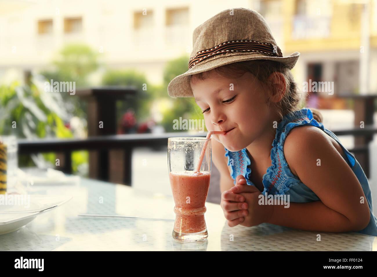 Il pensiero carino kid ragazza bere succhi gustosi nel ristorante di strada Immagini Stock