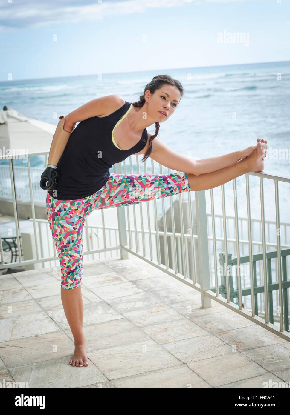 Razza mista amputato atleta stretching sul balcone Foto Stock