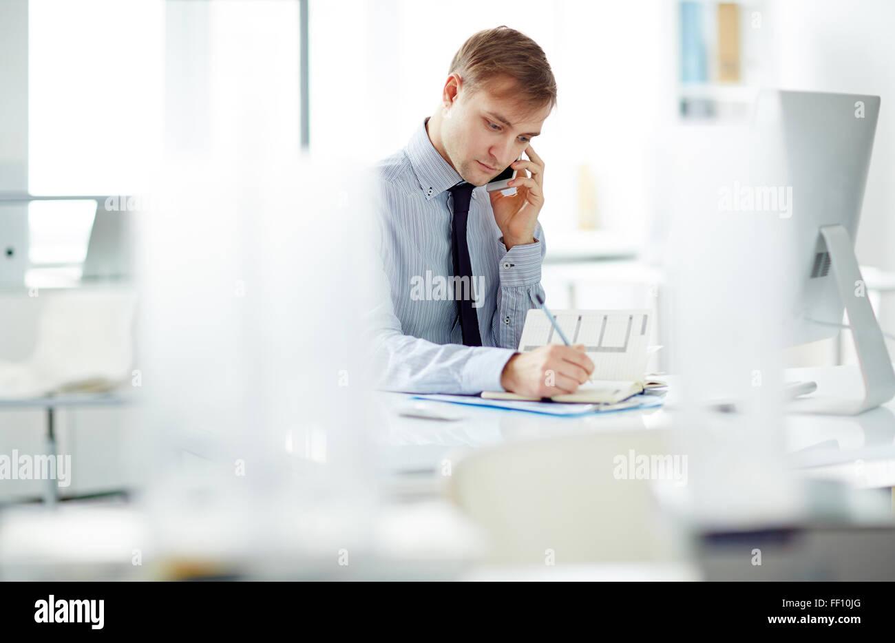 Giovane imprenditore che parla al telefono e di rendere note in Blocco note in Office Immagini Stock