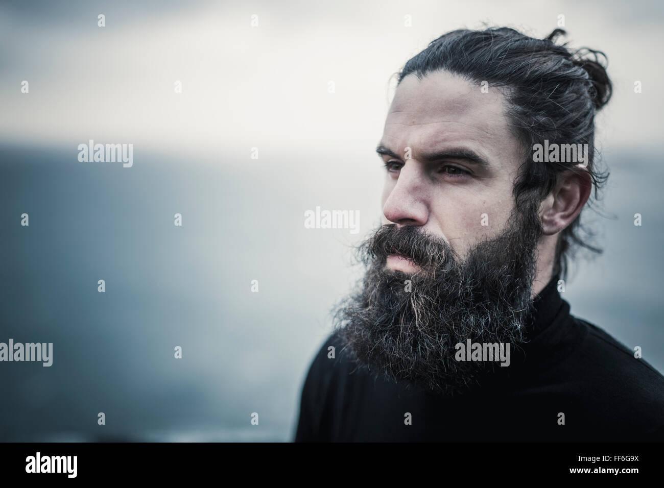 Un uomo con il pieno di barba e baffi e capelli neri rottamato indietro dal suo volto. Immagini Stock