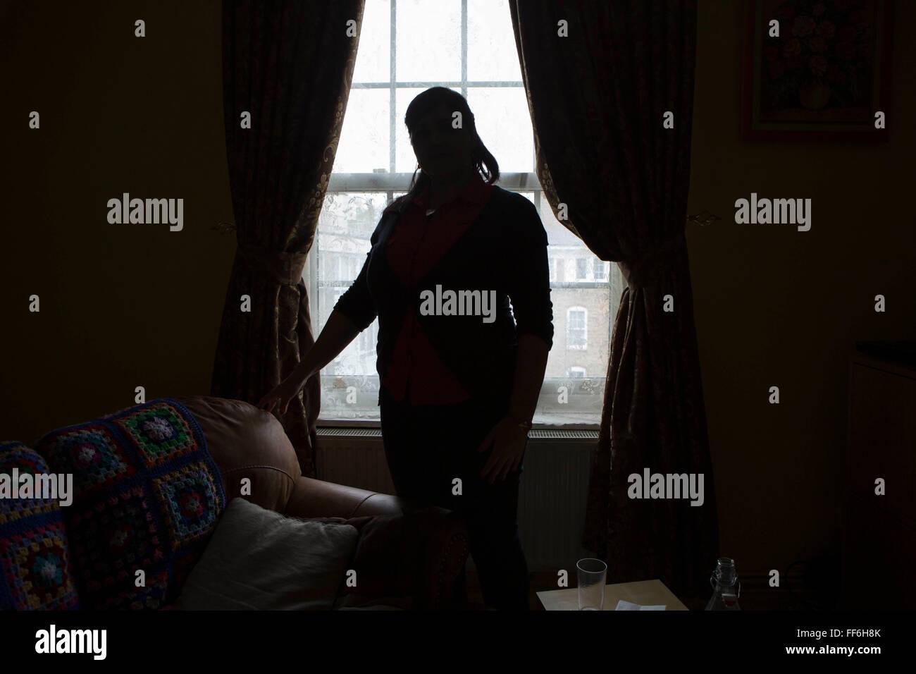 Una signora non identificato si erge profilarsi davanti al suo soggiorno finestra. Isolamento e le questioni relative Immagini Stock