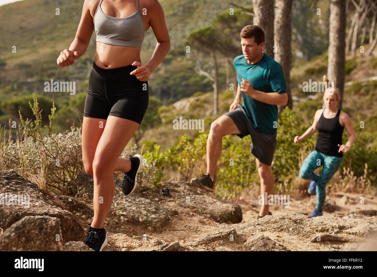 Montare i giovani in esecuzione su per una collina. Trail Running training. Giovani e montare gli atleti in funzione Immagini Stock