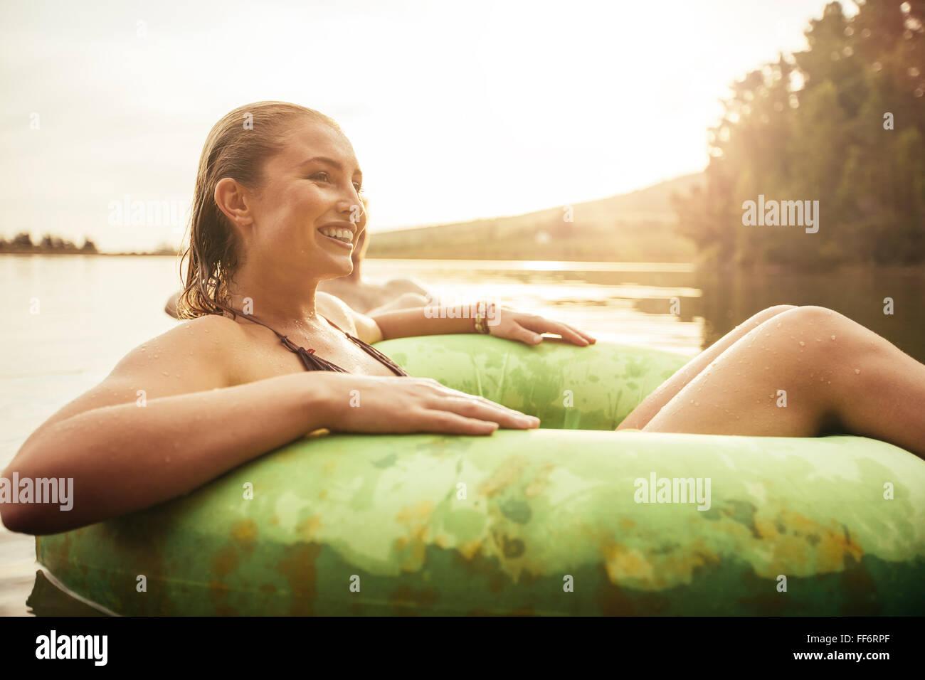 Ritratto di felice giovane donna nel lago su anello gonfiabile che guarda lontano e sorridente. Giovane ragazza Immagini Stock