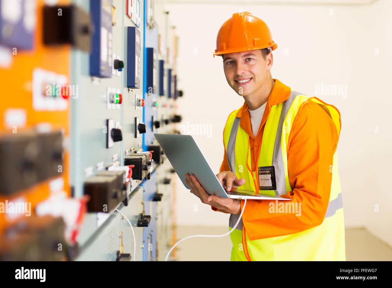 Sorridente ingegnere maschio con computer portatile nella sala di controllo Immagini Stock