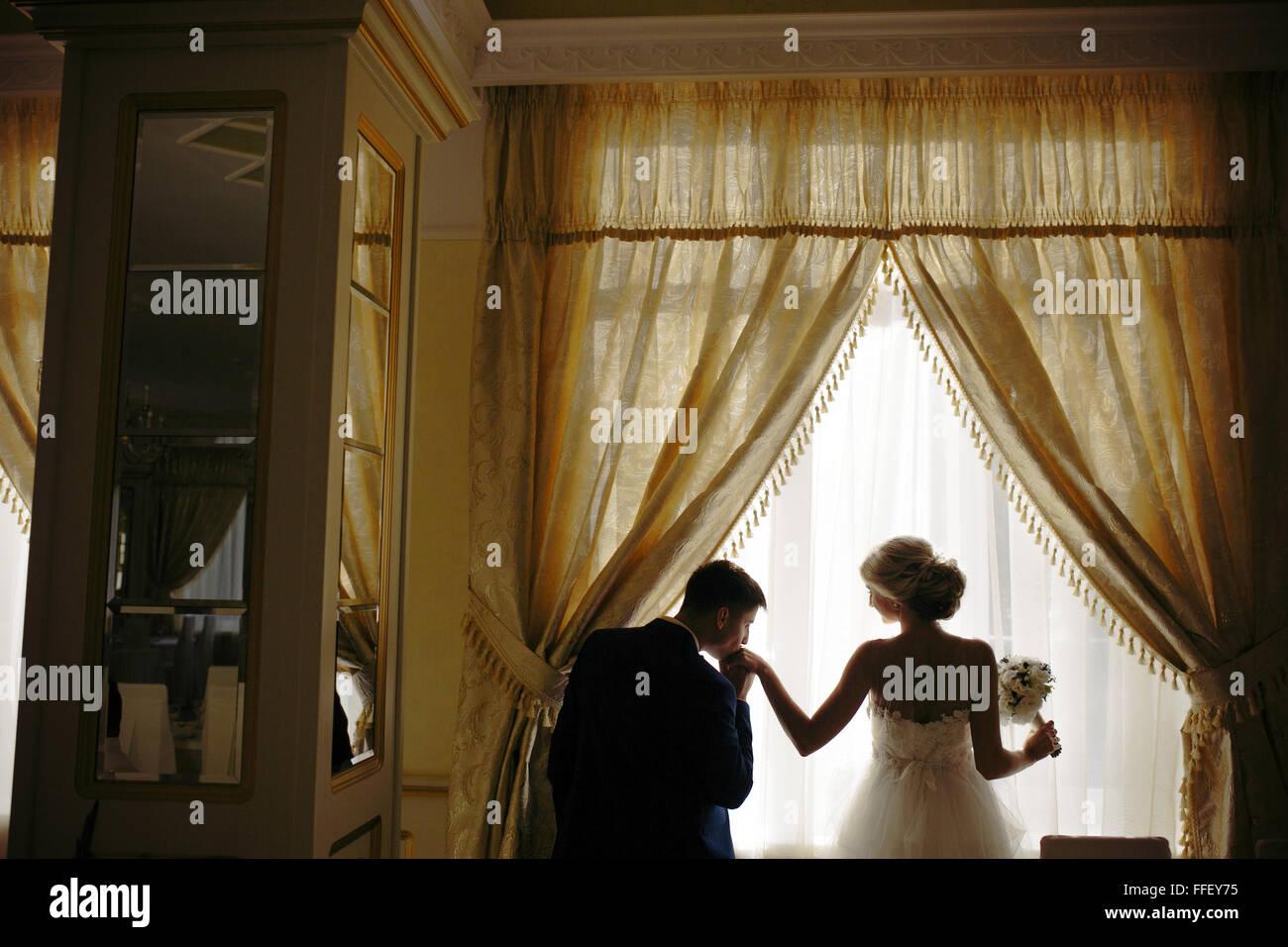 Sposa e lo sposo in piedi nella parte anteriore della finestra Immagini Stock