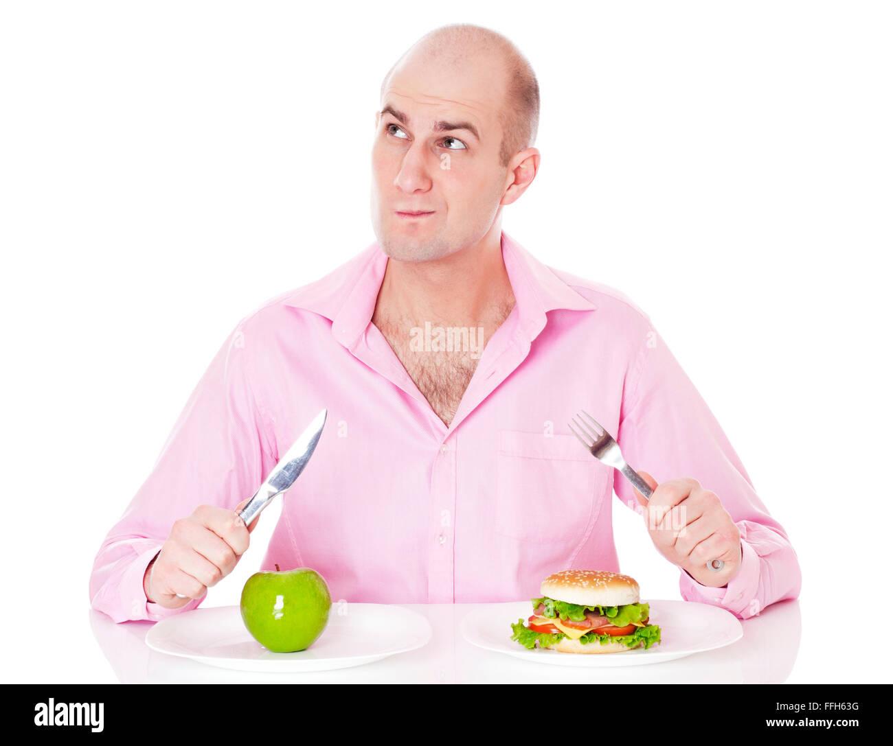 Uomo caucasico indeciso se egli sta andando andare per Apple o per l' hamburger, isolato su sfondo bianco. Immagini Stock