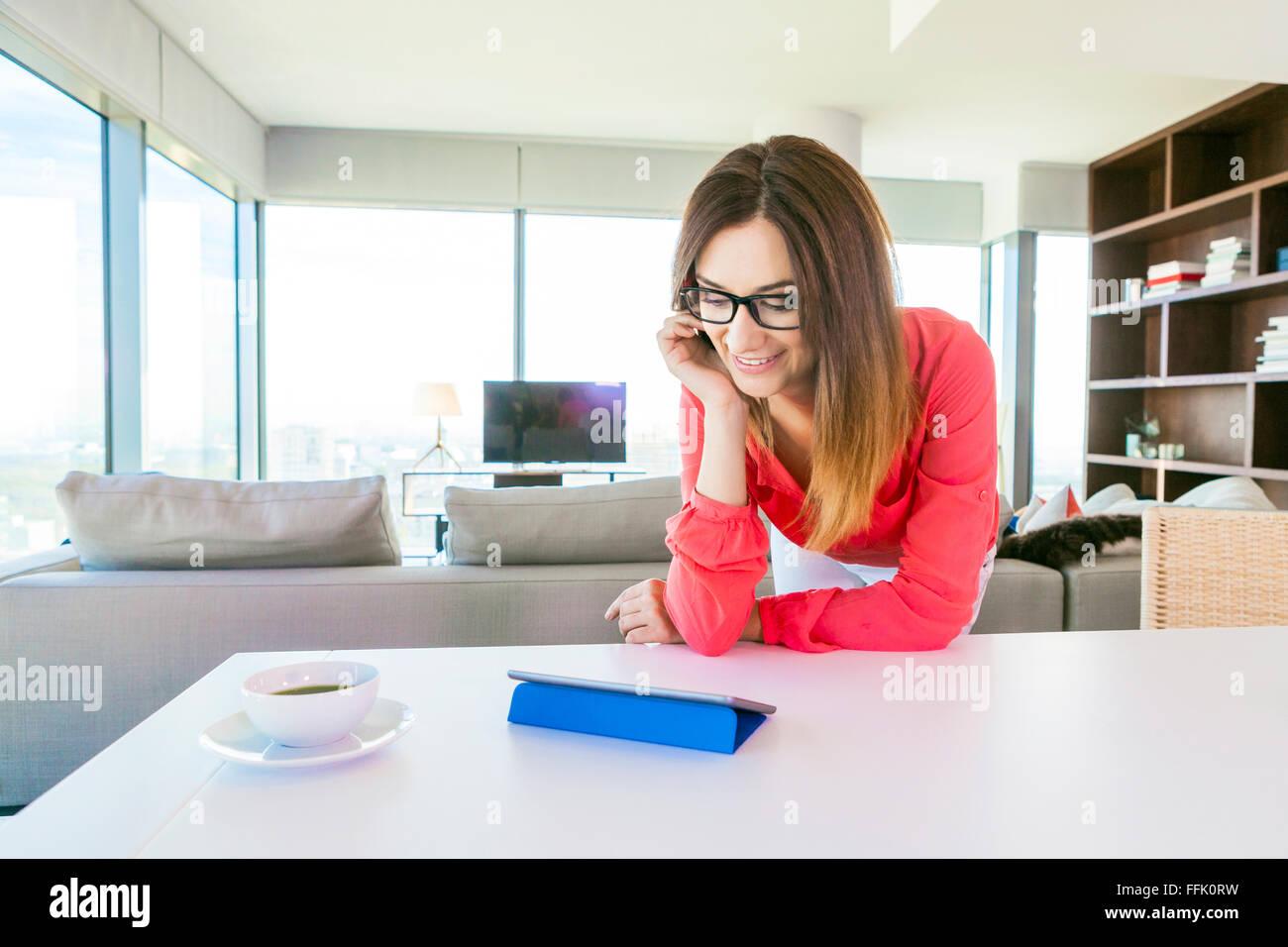 Donna in appartamento navigando in rete con tavoletta digitale Immagini Stock