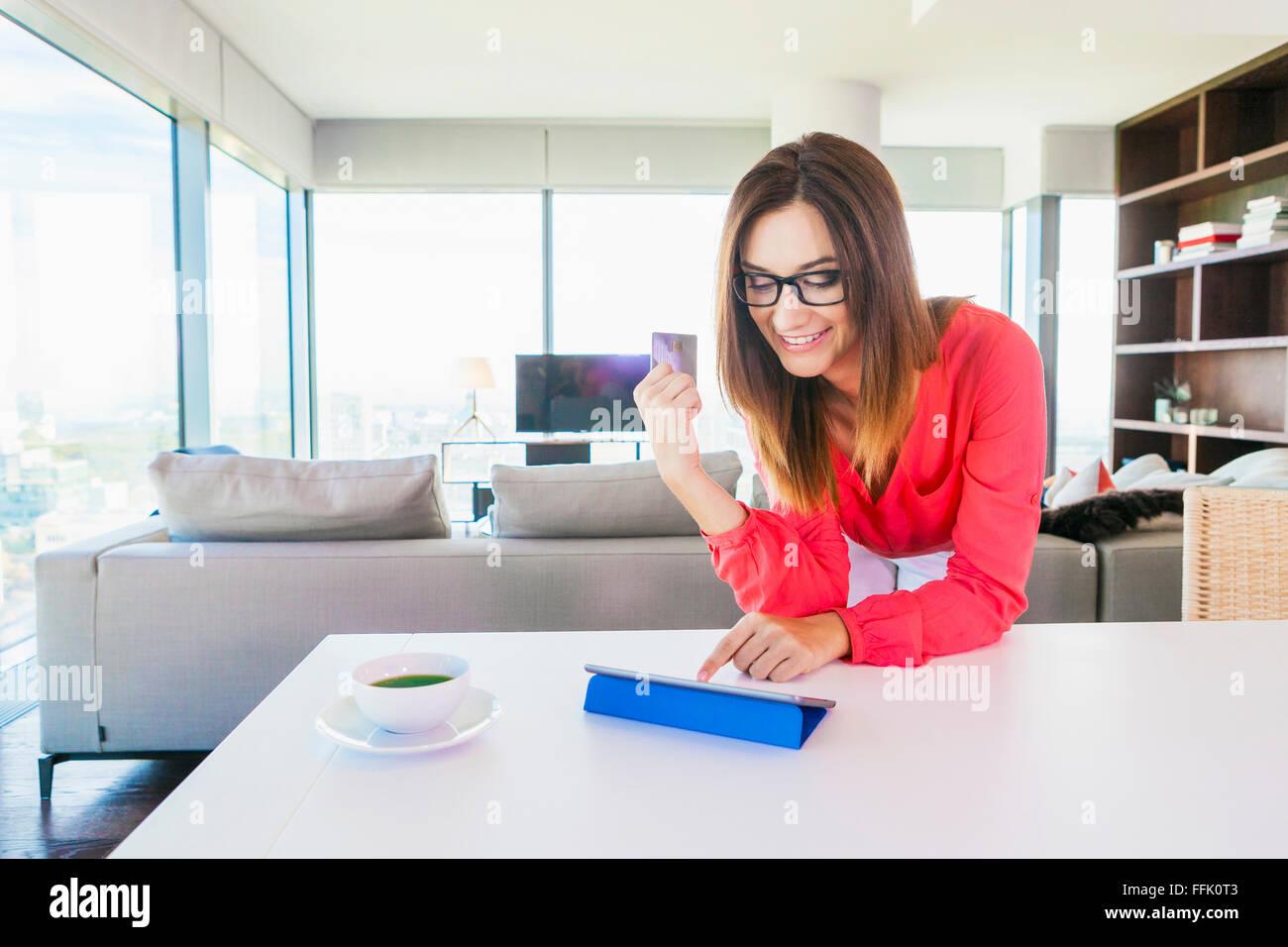 Donna in appartamento shopping online con tavoletta digitale Immagini Stock