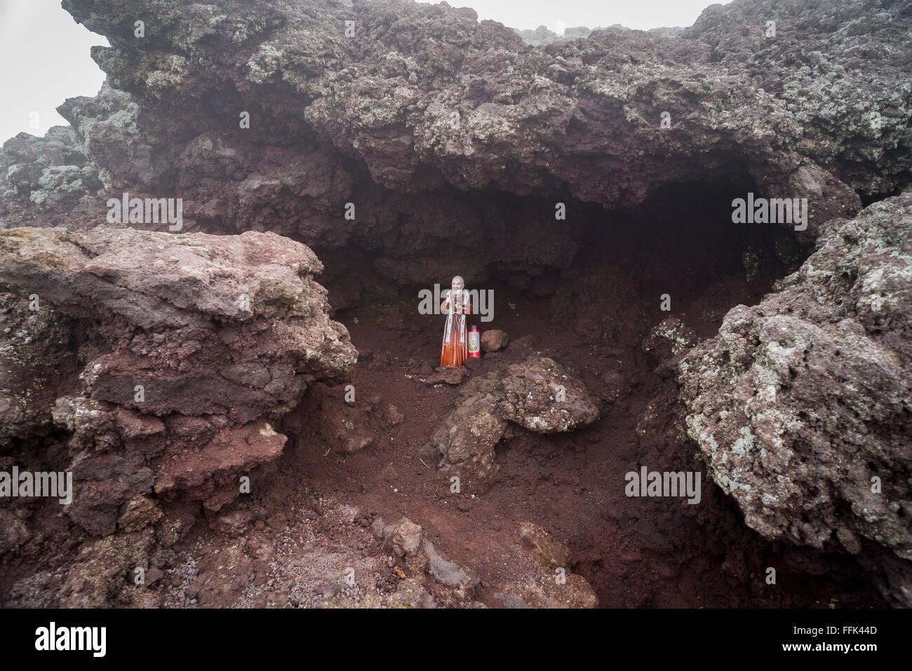 Una statuetta di Padre Pio collocato in una piccola grotta di lava vicino al cratere vulcanico presso la vetta del Immagini Stock