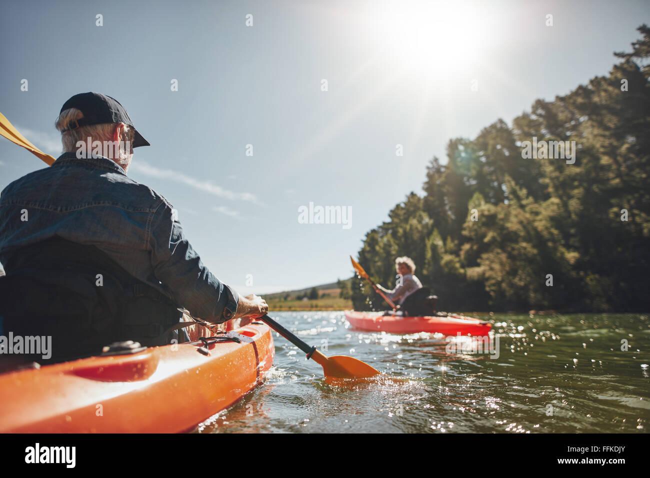 Immagine della coppia senior canoa nel lago in una giornata di sole. Kayakers nel lago di remata. Immagini Stock