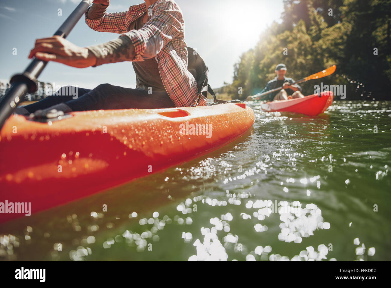 Immagine ritagliata della donna kayak con un uomo in background. Giovane canoa in un lago in un giorno di estate. Immagini Stock